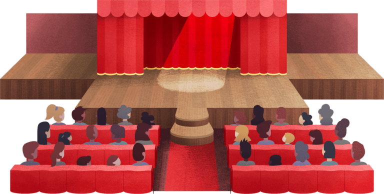 People seated in front of a stage with a spotlight shining in front of the red curtains